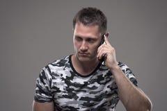 Σοβαρός απογοητευμένος νεαρός άνδρας που μιλά στο κινητό τηλέφωνο και που κοιτάζει κάτω στοκ φωτογραφίες
