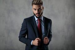 Σοβαρός επιχειρηματίας που κρατά το περιλαίμιο του κοστουμιού του στοκ εικόνα με δικαίωμα ελεύθερης χρήσης