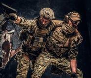 Σύγκρουση αγώνα, ειδική αποστολή Ο στρατιωτικός φέρνοντας συμπαίκτης στρατιωτών από το πεδίο μάχη Φωτογραφία στούντιο ενάντια στο στοκ εικόνες