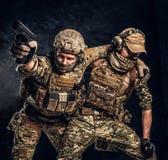 Σύγκρουση αγώνα, ειδική αποστολή Ο στρατιωτικός φέρνοντας συμπαίκτης στρατιωτών από το πεδίο μάχη Φωτογραφία στούντιο ενάντια στο στοκ φωτογραφία