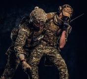 Σύγκρουση αγώνα, ειδική αποστολή Ο στρατιωτικός φέρνοντας συμπαίκτης στρατιωτών από το πεδίο μάχη Φωτογραφία στούντιο ενάντια στο στοκ εικόνα με δικαίωμα ελεύθερης χρήσης