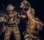 Σύγκρουση αγώνα, ειδική αποστολή, υποχώρηση Ο στρατιωτικός γιατρός διασώζει τον πληγωμένο συμπαίκτη του που φέρνει τον από το πεδ στοκ εικόνες