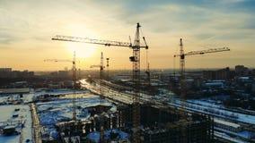 Σύγχρονοι γερανοί οικοδόμησης που λειτουργούν σε ένα εργοτάξιο οικοδομής κοντά σε έναν δρόμο απόθεμα βίντεο