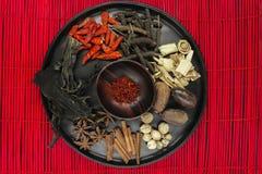 Σύνθεση μιγμάτων των διάφορων εξωτικών ξηρών καρυκευμάτων στο μαύρο στρογγυλό κύπελλο στο κόκκινο χαλί μπαμπού στοκ φωτογραφία με δικαίωμα ελεύθερης χρήσης