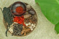 Σύνθεση μιγμάτων των διάφορων εξωτικών ξηρών καρυκευμάτων στο φυσικό κύπελλο μπαμπού στο χαλί μπαμπού και το πράσινο τροπικό φύλλ στοκ φωτογραφία με δικαίωμα ελεύθερης χρήσης