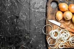 Σύνολο και δαχτυλίδια των φρέσκων κρεμμυδιών σε έναν τέμνοντα πίνακα με ένα μαχαίρι στοκ εικόνες