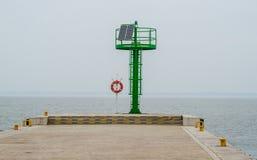 Στάση Lifebuoy και μια πράσινη επιγραφή λιμένων σε ένα μικρό λιμάνι στοκ εικόνα