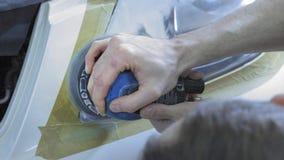 Στίλβωση προβολέων, επεξεργασία των φω'των αυτοκινήτων Ένας εργαζόμενος υπηρεσιών αυτοκινήτων γυαλίζει τον προβολέα ενός επιβατικ απόθεμα βίντεο