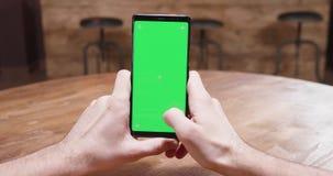 Στατικός πυροβολισμός των αρσενικών χεριών που κρατούν ένα τηλέφωνο με την πράσινη επίδειξη οθόνης απόθεμα βίντεο