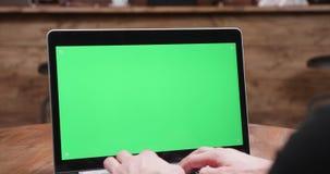 Στατικός πυροβολισμός των αρσενικών χεριών που δακτυλογραφούν σε ένα σύγχρονο lap-top με την πράσινη οθόνη στην επίδειξη απόθεμα βίντεο