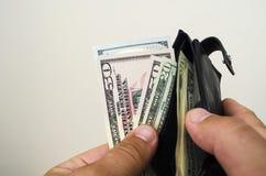 Στα χέρια ενός πορτοφολιού στο οποίο αμερικανικοί λογαριασμοί δολαρίων στοκ εικόνα με δικαίωμα ελεύθερης χρήσης