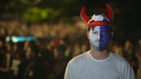 Στενός επάνω ανεμιστήρων Γάλλου το κακό παιχνίδι, εξετάζοντας τη κάμερα 4K με το πρόσωπο χρωμάτων απόθεμα βίντεο