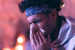 Στενό πορτρέτο του νεαρού άνδρα του αφρικανικής καταγωγής με την πετσέτα κοντά στο πρόσωπό του στο θολωμένο υπόβαθρο στοκ φωτογραφίες