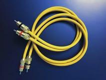 Στερεοφωνικό ακουστικό κίτρινο καλώδιο επέκτασης που απομονώνεται στο μπλε υπόβαθρο στοκ φωτογραφία με δικαίωμα ελεύθερης χρήσης