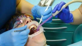 Στο σύγχρονο γραφείο οδοντιάτρων Κινηματογράφηση σε πρώτο πλάνο που πυροβολείται της οδοντικής διαδικασίας Θηλυκός ασθενής που πα απόθεμα βίντεο