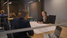 Στο σύγχρονο γραφείο τρία το προσωπικό στον πίνακα φαίνεται το έγγραφο σχεδίων και η συζήτηση απόθεμα βίντεο