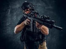 Στρατιώτης ειδικών δυνάμεων που φορά τη πανοπλία και το κράνος με τη νυχτερινή όραση που κρατά ένα επιθετικό τουφέκι Φωτογραφία σ στοκ φωτογραφία με δικαίωμα ελεύθερης χρήσης