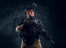 Στρατιώτης ειδικών δυνάμεων που φορά τη πανοπλία και το κράνος με τη νυχτερινή όραση που κρατά ένα επιθετικό τουφέκι Φωτογραφία σ στοκ εικόνες