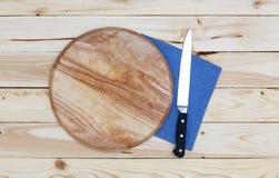 Στρογγυλός τέμνων πίνακας με ένα μαχαίρι σε έναν ξύλινο πίνακα, τοπ άποψη στοκ φωτογραφίες