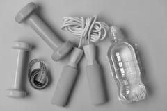 Σχοινί άλματος και barbells δίπλα στο μπουκάλι και την ταινία μέτρου στοκ εικόνες