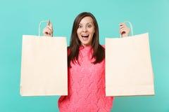 Συγκινημένη έκπληκτη νέα γυναίκα στην πλεκτή ρόδινη εκμετάλλευση πουλόβερ στην κενή τσάντα συσκευασίας χεριών με τις αγορές μετά  στοκ φωτογραφία με δικαίωμα ελεύθερης χρήσης