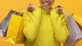 Συγκινημένη νέα γυναίκα στις μοντέρνες κίτρινες τσάντες αγορών εκμετάλλευσης πουλόβερ, έκπτωση φιλμ μικρού μήκους