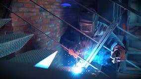 Συγκόλληση μετάλλων Αρσενικός οξυγονοκολλητής που λειτουργεί στην προστατευτική μάσκα στα σκαλοπάτια σιδήρου κατασκευή έννοιας βι απόθεμα βίντεο