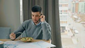 Συζήτηση επιχειρηματιών χαμόγελου στο τηλέφωνο, που τρώει τη συνεδρίαση μεσημεριανού γεύματος στο γραφείο στον καφέ φιλμ μικρού μήκους