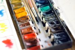 Συμπαγής παλέτα watercolor και τέσσερις βούρτσες από την τρίχα σκιούρων στοκ φωτογραφία