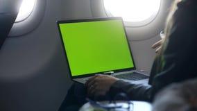 Συνεδρίαση γυναικών με το κενό lap-top οθόνης στην καμπίνα αεροπλάνων φιλμ μικρού μήκους