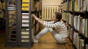 Συνεδρίαση κοριτσιών στο πάτωμα και επιλογή ενός βιβλίου απόθεμα βίντεο