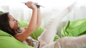 Συνεδρίαση μικρών κοριτσιών στην καρέκλα που χρησιμοποιεί την ευτυχή διασκέδαση lap-top κλείστε επάνω το σπίτι παιχνιδιού τεχνολο απόθεμα βίντεο