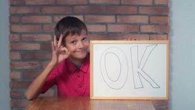 Συνεδρίαση παιδιών στην εκμετάλλευση γραφείων flipchart με να γράψει εντάξει επάνω στοκ φωτογραφίες