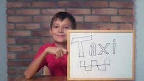 Συνεδρίαση παιδιών στην εκμετάλλευση γραφείων flipchart με την εγγραφή του ταξί στοκ φωτογραφίες