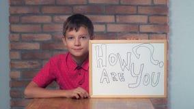Συνεδρίαση παιδιών στην εκμετάλλευση γραφείων flipchart με την εγγραφή πώς α στοκ φωτογραφία με δικαίωμα ελεύθερης χρήσης