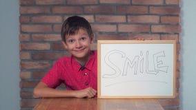 Συνεδρίαση παιδιών στην εκμετάλλευση γραφείων flipchart με το χαμόγελο εγγραφής στοκ φωτογραφία με δικαίωμα ελεύθερης χρήσης