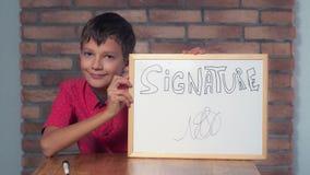 Συνεδρίαση παιδιών στην εκμετάλλευση γραφείων flipchart με το signa εγγραφής στοκ φωτογραφίες