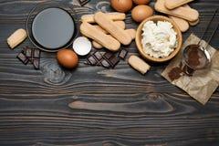 Συστατικά για το tiramisu μαγειρέματος - μπισκότα, mascarpone, κρέμα, ζάχαρη, κακάο, καφές και αυγό μπισκότων Savoiardi στοκ φωτογραφίες