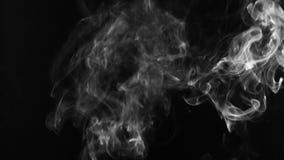 Συστροφές του άσπρου καπνού σε ένα μαύρο υπόβαθρο φιλμ μικρού μήκους
