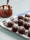 Σπιτικές υγιείς τρούφες ή σφαίρες σοκολάτας Paleo ακατέργαστες με τα καρύδια, τις ημερομηνίες και την καρύδα στο ελαφρύ υπόβαθρο στοκ φωτογραφία με δικαίωμα ελεύθερης χρήσης