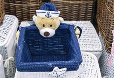 Ψάθινο καλάθι πλυντηρίων με μια teddy αρκούδα θαλάσσιο σε ομοιόμορφο στοκ φωτογραφίες