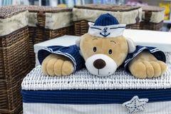 Ψάθινο καλάθι πλυντηρίων με μια teddy αρκούδα θαλάσσιο σε ομοιόμορφο στοκ εικόνες
