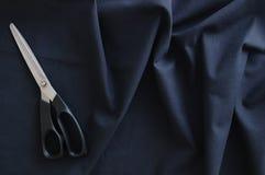 Ψαλίδι στο μαύρο τσαλακωμένο ύφασμα επάνω από την όψη Κινηματογράφηση σε πρώτο πλάνο στοκ εικόνες