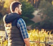 Ψαράς με μια περιστροφή και ένα δόλωμα που πιάνουν τα ψάρια σε μια λίμνη ή έναν ποταμό Άτομο σε ένα Σαββατοκύριακο με έναν δρόμο  στοκ φωτογραφία με δικαίωμα ελεύθερης χρήσης