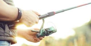 Ψαράς με μια περιστροφή και ένα δόλωμα που πιάνουν τα ψάρια σε μια λίμνη ή έναν ποταμό Άτομο σε ένα Σαββατοκύριακο με έναν δρόμο  στοκ φωτογραφίες