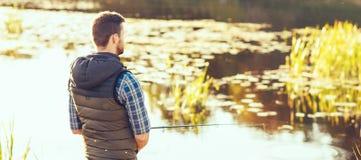 Ψαράς με μια περιστροφή και ένα δόλωμα που πιάνουν τα ψάρια σε μια λίμνη ή έναν ποταμό Άτομο σε ένα Σαββατοκύριακο με έναν δρόμο  στοκ εικόνες με δικαίωμα ελεύθερης χρήσης