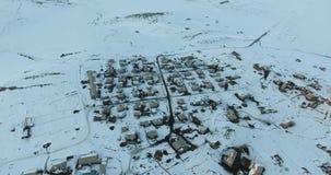 Ψαράς πάγου στην παγωμένη lakeAerial άποψη χειμερινών βουνών του όμορφου χωριού φιλμ μικρού μήκους