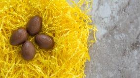 Τέσσερα αυγά Πάσχας σοκολάτας στην κίτρινη χλόη Πάσχας σε έναν μαρμάρινο μετρητή στοκ εικόνες