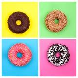 Τέσσερα διαφορετικά donuts στη φωτεινή πολύχρωμη τοπ άποψη υποβάθρου στοκ φωτογραφία με δικαίωμα ελεύθερης χρήσης