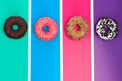 Τέσσερα διαφορετικά donuts στη φωτεινή πολύχρωμη τοπ άποψη υποβάθρου στοκ εικόνα με δικαίωμα ελεύθερης χρήσης
